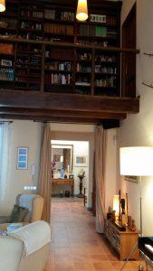Salón con biblioteca a doble altura en casa de campo